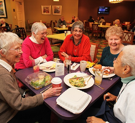 group of senior women sitting at dinner table laughing