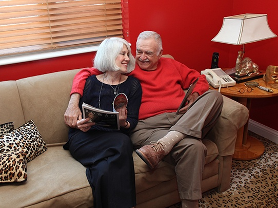 senior couple at admiral at the lake on couch smiling