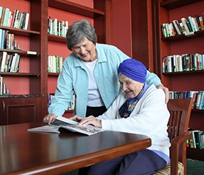woman standing next to older woman who is reading a book